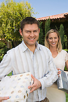 Mid-adult couple holding birthday presents, smiling