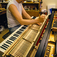 Piano tuner gives a baby grand it's final check before sending the piano out at the Steinway Piano factory, Astoria, Queens, New York.