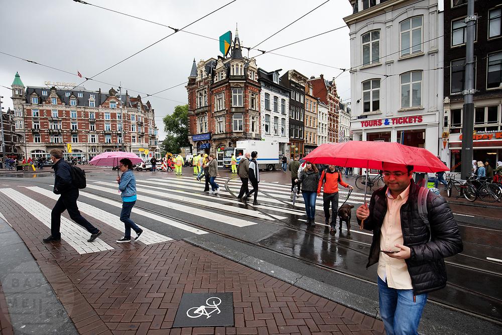 Voetgangers steken het Muntplein in Amsterdam over in de regen.<br /> <br /> Pedestrians cross the Munt Square in Amsterdam in the rain.