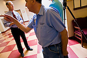 13 OCTOBER 2010 - TUCSON, AZ: A janitor walks past Terry Goddard while Goddard gives a TV interview before a candidate forum in Tucson. Goddard spent the day in Tucson campaigning. Goddard lost the election to sitting Governor Jan Brewer, a conservative Republican.     PHOTO BY JACK KURTZ