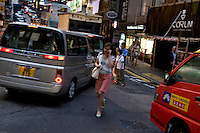 Woman on the phone crossing Wellington street, Central, Hong Kong.