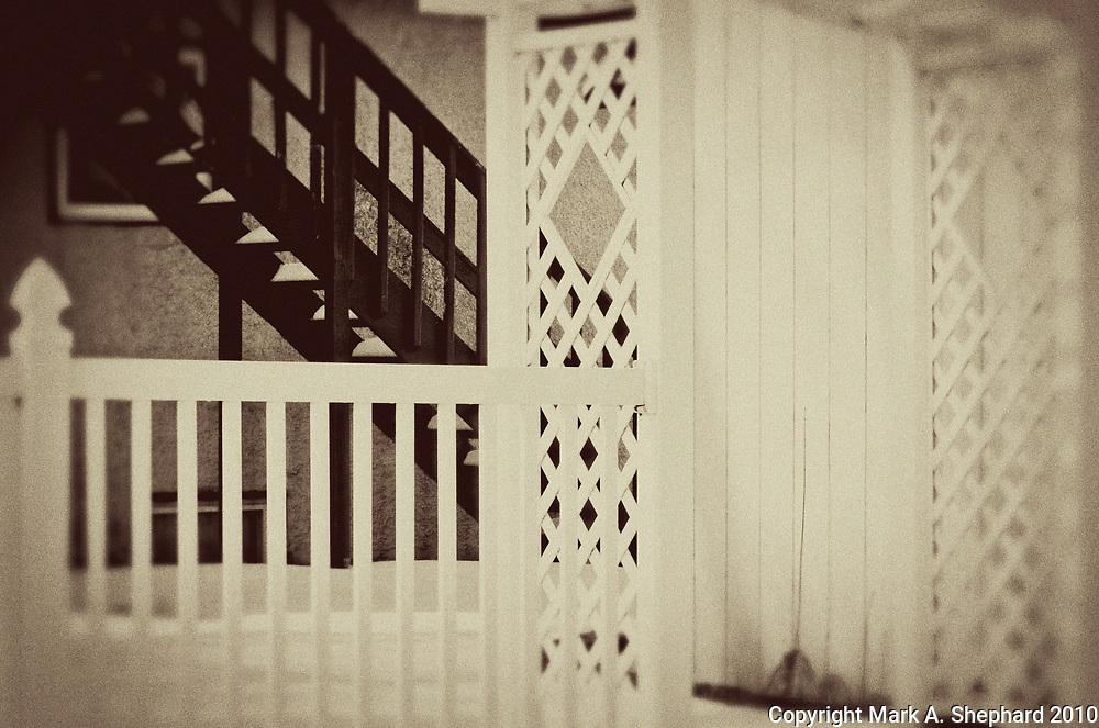 A white fence and a black staircase contrast each other against a February 2010 Nappanee, Indiana landscape. This is a vintage Photoshop treatment. (Photo By Mark Shephard)