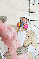 Male contractor wearing dust mask while holding sponge at construction site