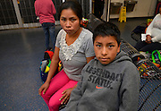 A Guatemalan woman and her 10-year-old son, who crossed illegally from Mexico into the United States, look through belongings at the bus station in Tucson, Arizona, USA.  U.S. Border Patrol agents released the two to travel to a secondary location in the states where their immigration status will be addressed.