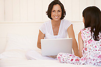 Mother using lap top sitting with daughter on bed