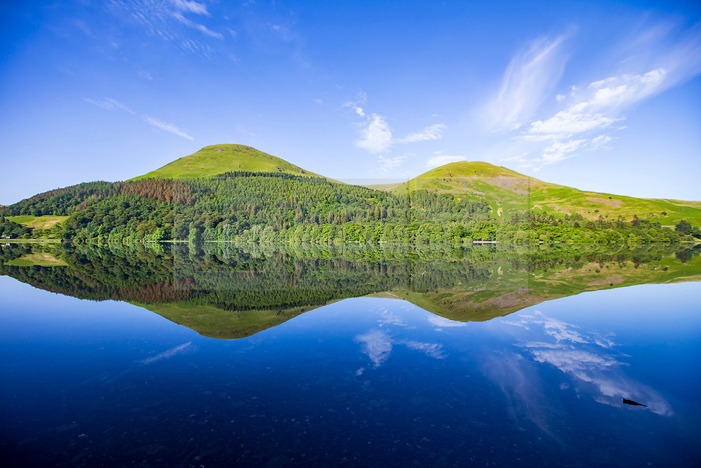 © Licensed to London News Pictures. 07/06/2018. Buttermere UK. Mountains around  Loweswater lake reflect into the still water this morning on a sunny day in Cumbria. Photo credit: Andrew McCaren/LNP