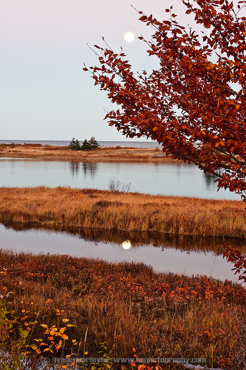 The moon and its reflection are seen at dusk during fall on Cape Breton Island in Nova Scotia, Canada.
