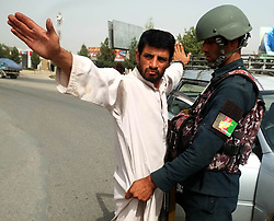 September 16, 2018 - Kandahar, Afghanistan - An Afghan security force member checks a man at a security checkpoint in Kandahar city, capital of Kandahar province, Afghanistan. Unknown armed militants gunned down a district chief and his son in the southern Kandahar province on Saturday, an official said. (Credit Image: © Sanaullah Seiam/Xinhua via ZUMA Wire)