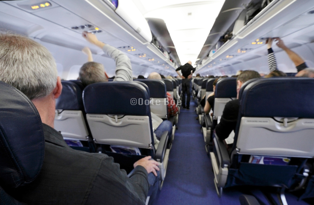inside airplane economy class with passengers