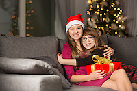 Happy girl hugging sister on sofa during Christmas