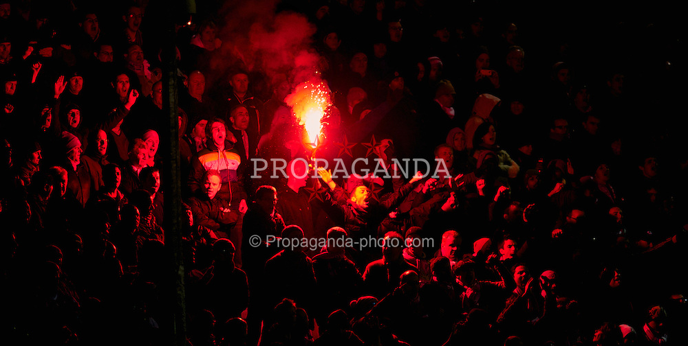 LILLE, FRANCE - Thursday, March 11, 2010: A Liverpool supporter with a flare urges his team on against LOSC Lille Metropole during the UEFA Europa League Round of 16 1st Leg match at the Stadium Lille-Metropole. (Photo by David Rawcliffe/Propaganda)