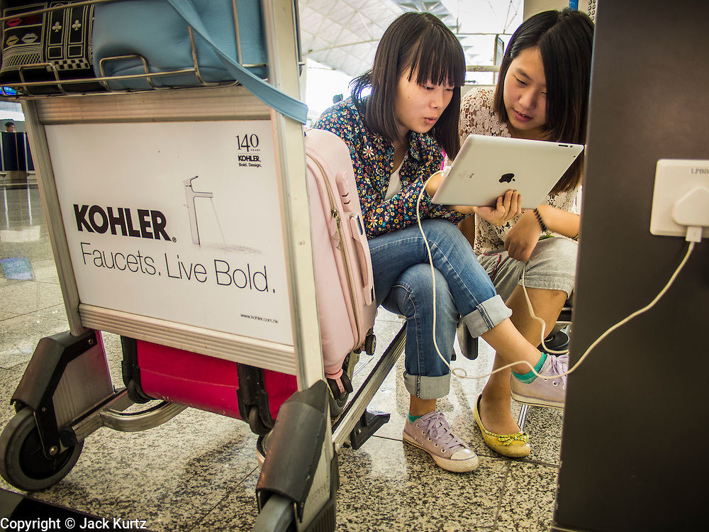 14 AUGUST 2013 - HONG KONG: Women waiting for a flight in Hong Kong watch a movie on an iPad in Hong Kong International Airport. Dozens of flights were delayed at one of the busiest airports in Asia and Hong Kong raised their alert to level 8, the highest, and closed schools and many businesses because of Severe Typhoon Utor. The storm passed within 260 kilometers of Hong Kong before making landfall in mainland China. Severe Typhoon Utor (known in the Philippines as Typhoon Labuyo) is an active tropical cyclone located over the South China Sea. The eleventh named storm and second typhoon of the 2013 typhoon season, Utor formed from a tropical depression on August 8. The depression was upgraded to Tropical Storm Utor the following day, and to typhoon intensity just a few hours afterwards. The Philippines, which bore the brunt of the storm, reported 1 dead in a mudslide and 23 fishermen missing at sea.   PHOTO BY JACK KURTZ