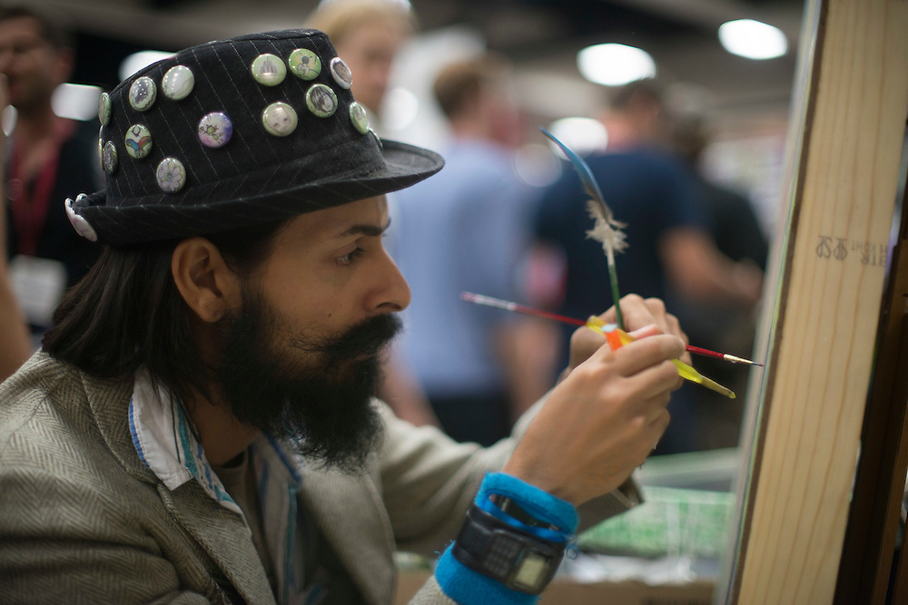 Irvine, CA based artist Arlyn Pillay works on a painting at his booth Friday at Comic-Con International in San Diego.  Pillar was selling prints and apparel at the pop-culture festival.
