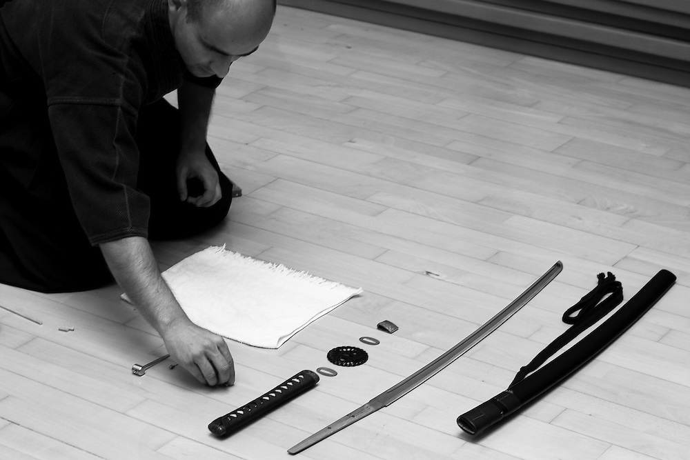 A Iaido student disassembles his katana for cleaning and refitting. Iaido students are required to take proper care of their weapons.