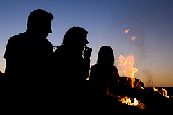 © Licensed to London News Pictures.27/08/15<br /> Saltburn, UK. <br /> <br /> NEIL WHITTLE and his wife Jenny from Saltburn sit with their daughter Mia, 6, as they eat marshmallows roasted over a fire on the beach at sunset.<br /> <br /> Photo credit : Ian Forsyth/LNP