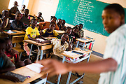Children listen to their teacher during class at the Youga primary school in the town of Youga, approximately 205 km southeast of Burkina Faso's capital Ouagadougou on Tuesday April 28, 2009. The school was renovated and expanded by BMC (Burkina Mining Company) when the Canadian-owned company started exploiting the gold mine outside of town.