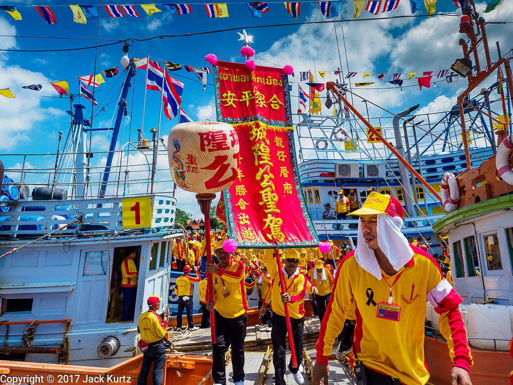"02 JUNE 2017 - SAMUT SAKHON, THAILAND:  Participants in the parade for the City Pillar Shrine get off a boat that carried them up the Tha Chin River during the procession for the City Pillar Shrine. The Chaopho Lak Mueang Procession (City Pillar Shrine Procession) is a religious festival that takes place in June in front of city hall in Samut Sakhon. The ""Chaopho Lak Mueang"" is  placed on a fishing boat and taken across the Tha Chin River from Talat Maha Chai to Tha Chalom in the area of Wat Suwannaram and then paraded through the community before returning to the temple in Samut Sakhon. Samut Sakhon is always known by its historic name of Mahachai.     PHOTO BY JACK KURTZ"
