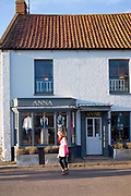 Stylish woman walking past boutique fashion shop in Burnham Market in North Norfolk, UK