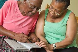 Carer and elderly visually impaired woman solving crossword.