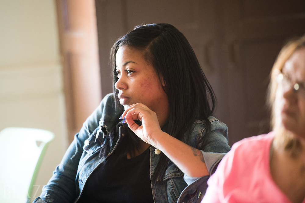 Tanay Mattis, a parent interested the new school, listens to a presentation at  E Prep and Village Prep Willard Campus in Cleveland.
