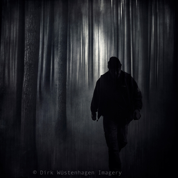 Silhouette oh a man walking through an abstract dark forest - composing with my own photos