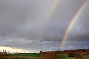 Double rainbow over hilly woodland and farmland in South West France