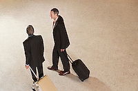 Two business men pulling suitcases in lobby