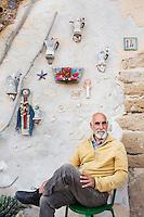 SCIACCA (AG), ITALIA - 22 APRILE 2015: Giulio Lorubbio (66 anni), detto Lulù, posa per un ritratto all'ingresso della sua abitazione nel Cortile Carini a Sciacca il 22 aprile 2015. Giulio Lorubbio è un artista autodidatta e istintuale che crea mosaici e collage tridimensionali con elementi riciclati trovati per strada, in spiaggia, in campagna: frammenti di vetro, pezzi di legno, reti, conchiglie, piastrelle rotte.