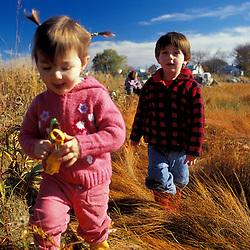 "Young friends play on a New Hampshire salt marsh. Tidal marsh.  ""Massacre Marsh."" Rye, NH"