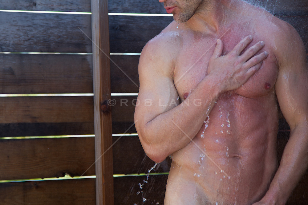 detail of a muscular man in an outdoor shower
