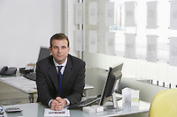 Business man sitting at desk in office portrait