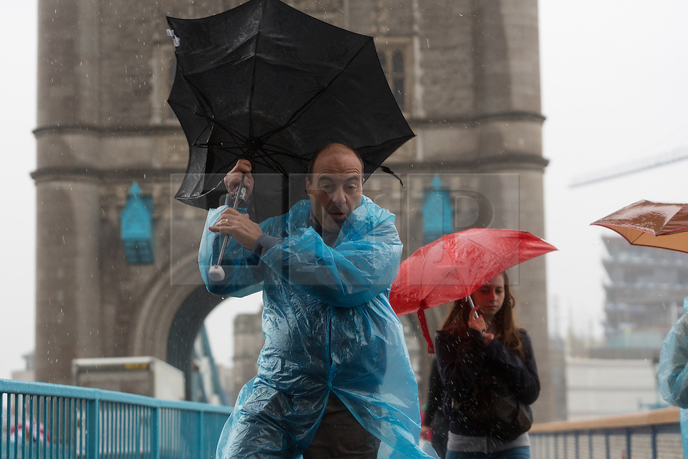 © Licensed to London News Pictures. 26/08/2014. London, UK. A man struggles with his umbrella during a gust of wind on Tower Bridge during heavy rain and strong wind. Heavy rain and cold weather are forecast for the rest of the day. Photo credit : Vickie Flores/LNP