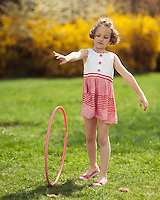 Young girl rolling hula hoop in park