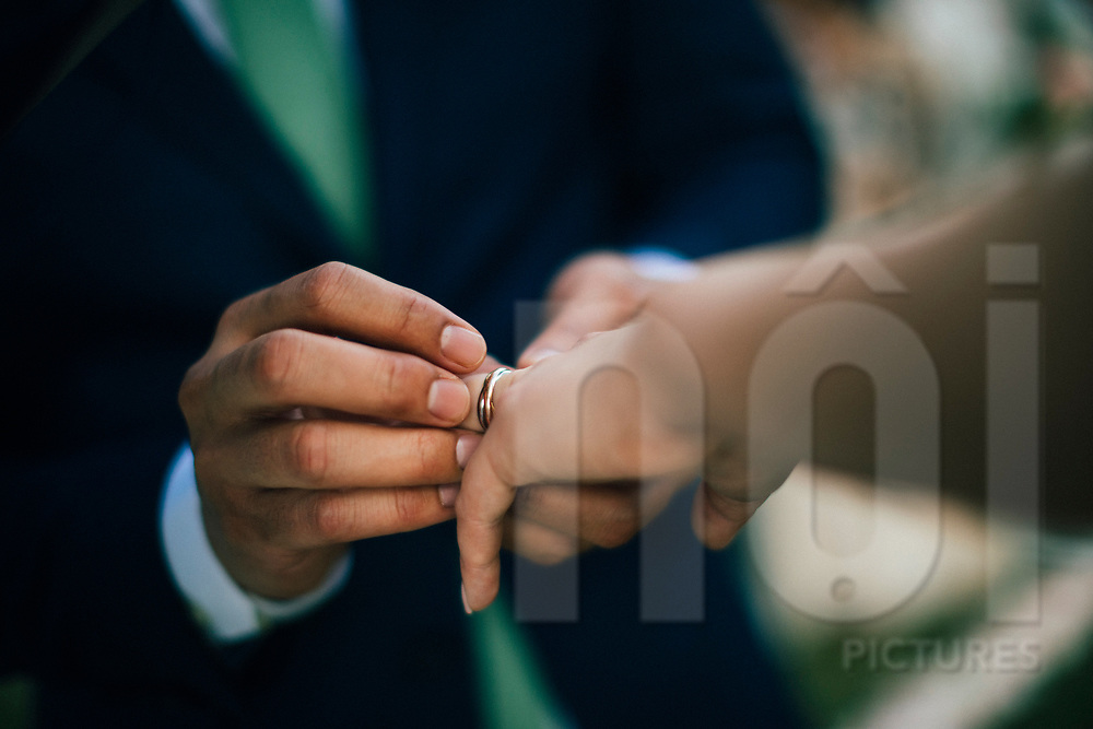 The groom slips the wedding ring onto the bride's finger, Ko Samui, Thailand, Southeast Asia
