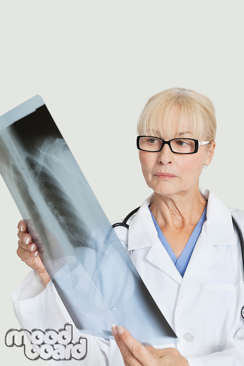 Senior female doctor examining x-ray over gray background