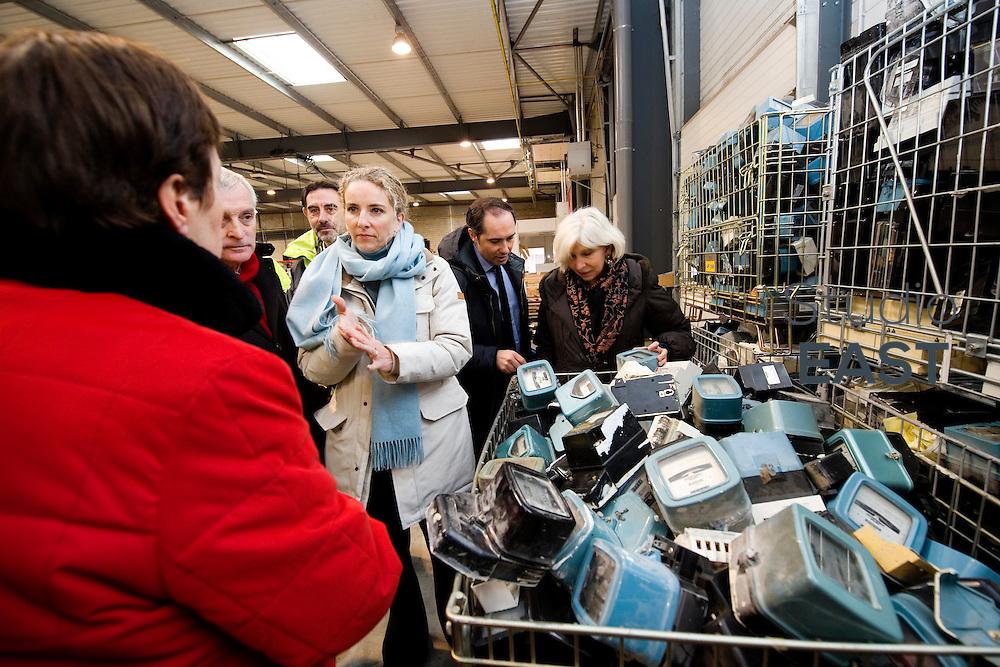 Mme Delphine Batho (2ème à partir de la gauche), accompagnée de Michèle Bellon (gauche) et de Laurence Tubiana (droite), découvre des compteurs électriques au rebut, durant la visite la plateforme Serval d'ERDF, à Gennevilliers, près de Paris, France, le 30 mars 2013. Photo : Lucas Schifres