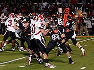 Junior Eric Kretz (64) holds off senior Matt Sacksteder (50) while senior Justin Weaver (10) throws a pass to senior Trent Koehler in the second quarter as the Wayne Warriors play the Beavercreek High School Beavers at the Frank Zink Field in Beavercreek, Friday, October 7, 2011.