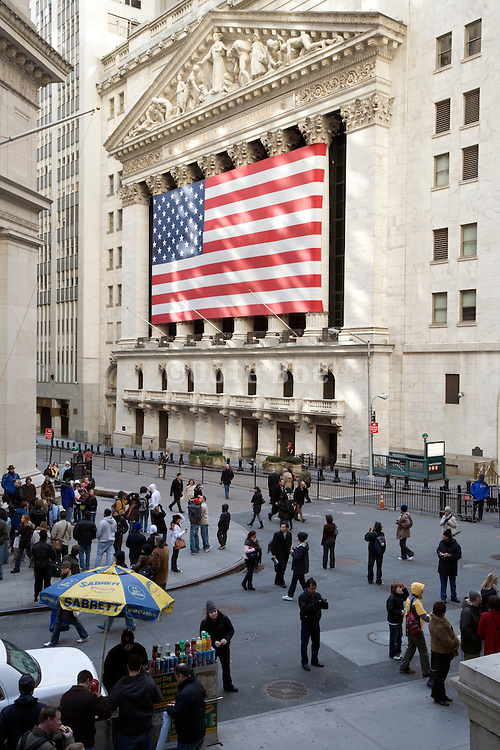 NY stock exchange on wall street with large American flag draped over the front facade