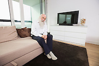 Sad senior man sitting on sofa in living room