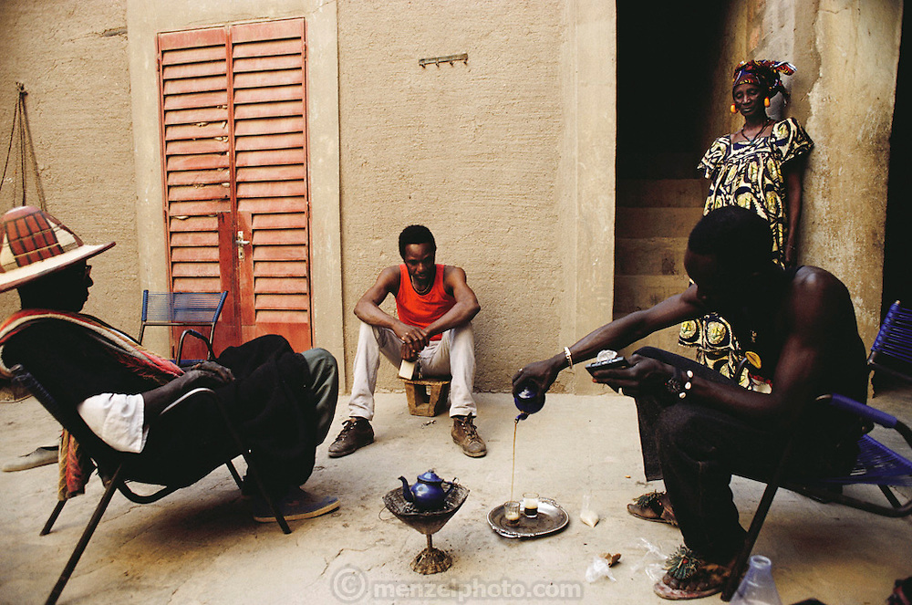 Albert Gano, who grew up in Kouakourou, Mali, is a guide for tourists in Djenne. Here he is vistiting his home village, taking tea with friends. Material World Project.
