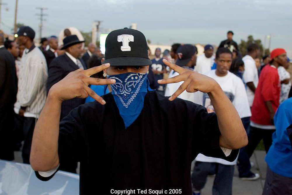 "Crip gangbanger at the Funeral services for Stanley ""Tookie"" Williams at Bethel A.M.E. Church in S. Central LA. About 2000 people attended the services which included many gang members. The funeral was a star studded event attended by Jesse Jackson and rapper-actor Snoop Dogg, Nation of Islam leader Louis Farrakhan, and Bianca Jagger.  Loudspeakers and a large TV screen brought the service to many of the onlookers who could not get inside the packed church.."