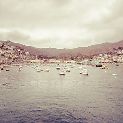 Picture of Avalon Bay in Catalina Island California. Photo is vintage 1970's toned and includes hillside buildings, businesses, and boats. Santa Catalina Island is part of Southern California in the United States.