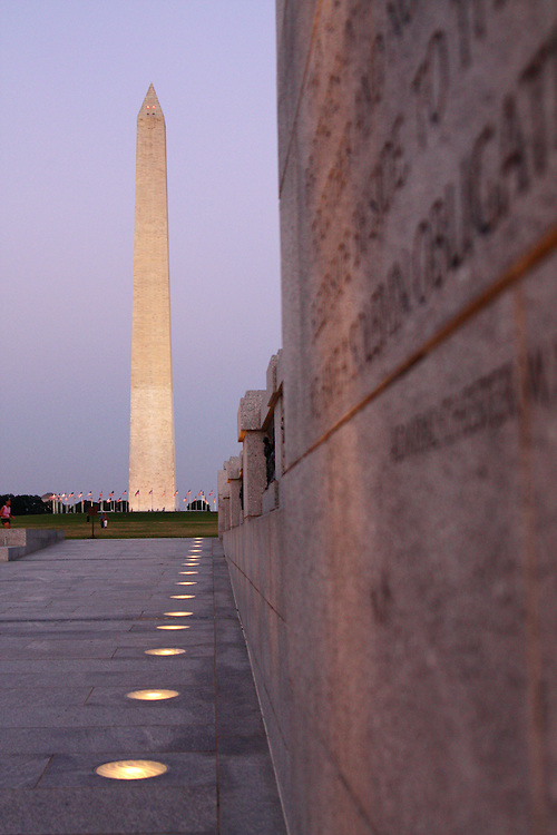 Dusk descends on the Washington Monument, framed here by a nearby wall at the World War II Memorial in Washington, DC