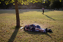 © Licensed to London News Pictures. 25/07/2019. London, UK. A couple sleep in early morning sunshine and heat in St James's Park in central London Today is expected to be another hot day with record breaking temperatures in parts of the UK  Photo credit: Peter Macdiarmid/LNP