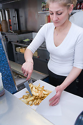 Bulgarian woman owner of fish and chip shop serving out a portion of chips from fryer,