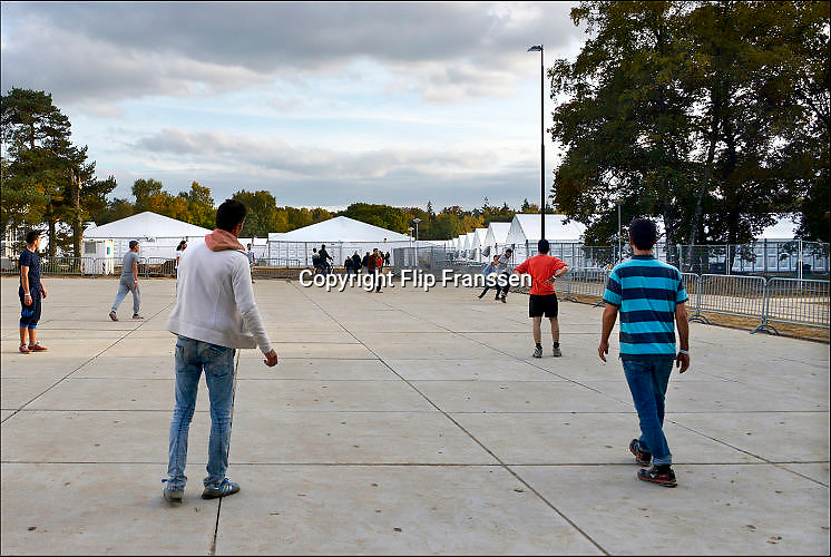 Nederland, Nijmegen, 25-10-2015 Bewoners, mannen van de noodopvang azc tentenkamp Heumensoord spelen een spelletje voetbal. Op de achtergrond de tenten waar zij verblijven.FOTO: FLIP FRANSSEN