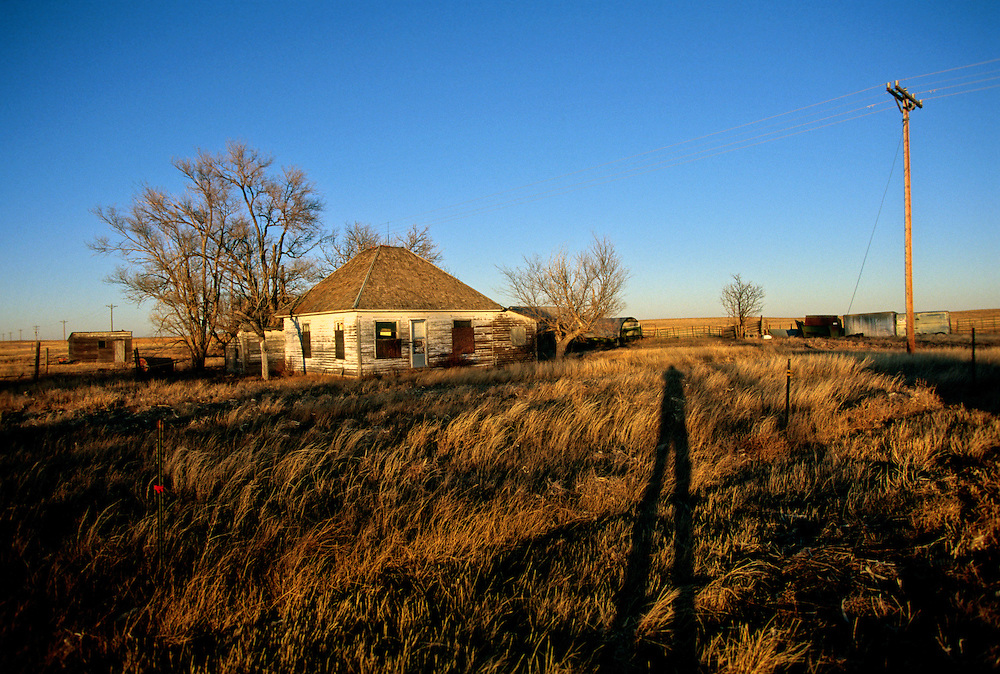 A shadow is cast across a vacant homestead in eastern Colorado