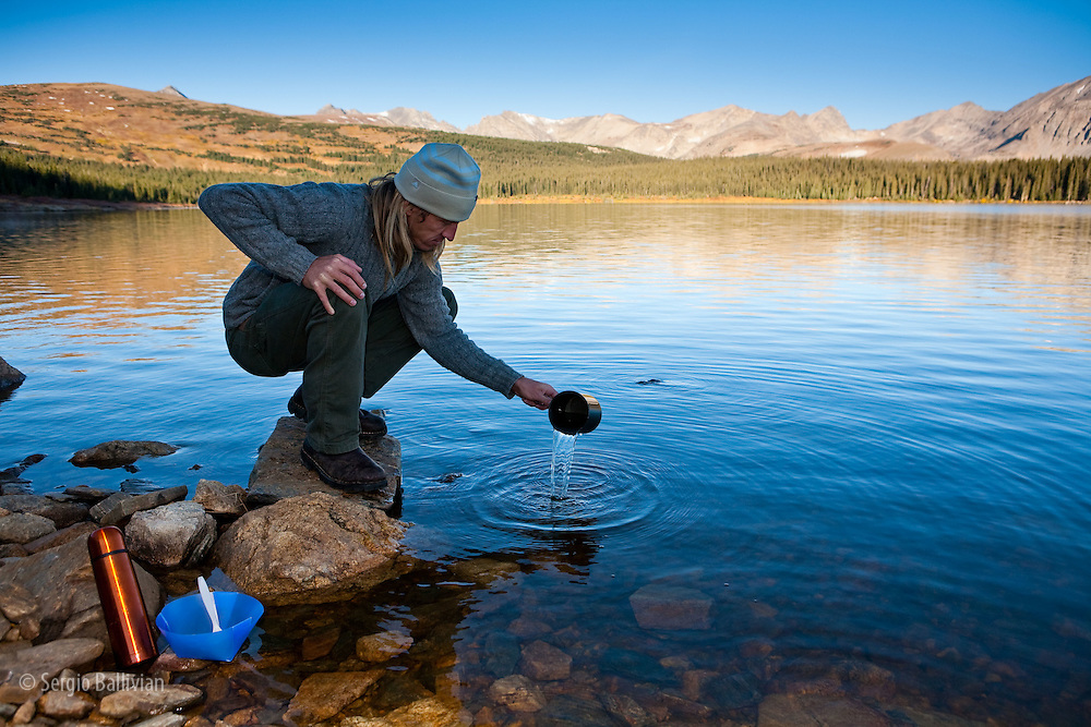 A camper gathers water for cooking in an alpine lake in Colorado.