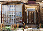 "Prominent windows front the finest home in Bodie, owned by James Stuart Cain from the 1890s - 1940s. Bodie is now California's official state gold rush ghost town. Jessie McGath originally built this house for his new wife in 1879, and JS Cain bought it in the 1890s. Cain moved to Bodie when he was 25 and built an empire starting with putting lumber barges on Mono Lake and transporting timber to support mine shafts, stoke boilers for machinery, build & heat buildings, and cook food. Cain eventually took control of the Stamp Mill though court action and went on to be the principal property owner and one of the richest men in town. Bodie State Historic Park lies in the Bodie Hills east of the Sierra Nevada mountain range in Mono County, near Bridgeport, California, USA. After W. S. Bodey's original gold discovery in 1859, profitable gold ore discoveries in 1876 and 1878 transformed ""Bodie"" from an isolated mining camp to a Wild West boomtown. By 1879, Bodie had a population of 5000-7000 people with 2000 buildings. At its peak, 65 saloons lined Main Street, which was a mile long. Bodie declined rapidly 1912-1917 and the last mine closed in 1942. Bodie became a National Historic Landmark in 1961 and Bodie State Historic Park in 1962."