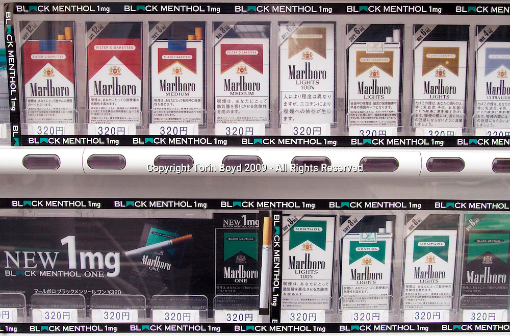 "These are Marlboro cigarettes being sold in vending machines on the streets of Tokyo. Many of these views show promotions for ""Marlboro One Black Menthol"", the new brand of smokes that contains only 1 MG of nicotine. This American brand is distributed in Japan through Philip Morris International (PMI) which In May 2005 ended it's 32 year license agreement with Japan Tobacco Inc. to sell the Marlboro brand in Japan. Currently there are some 30 million smokers in Japan and Marlboro is one of the top selling brands. The legal smoking age in Japan is age twenty and in order to purchase smokes from these vending machines, customers must use an age verification Taspo"" card (short for tobacco passport)..."